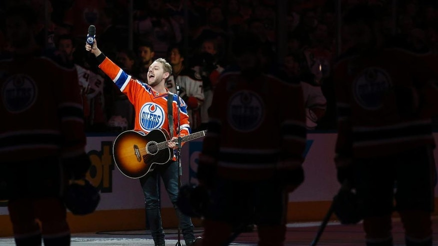 "Canadian country singer Brett Kissel holds his faulty microphone asking the crowd to sing the ""Star-Spangled Banner"" before the start of the Anaheim Ducks and the Edmonton Oilers NHL hockey round two playoff hockey game in Edmonton, Sunday, April 30, 2017. The U.S. national anthem got a unique rendition before the game when the microphone didn't work. Kissel attempted twice to sing the anthem before throwing his hands in the air and encouraging the crowd to sing with him. (Jeff McIntosh/The Canadian Press via AP)"