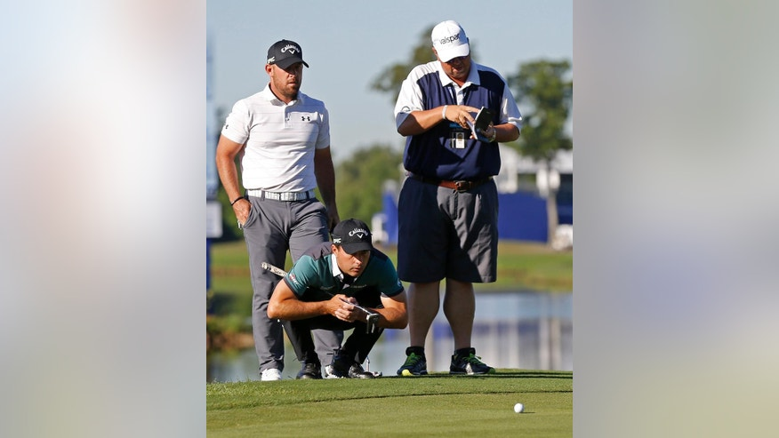 Kevin Kisner lines up a putt as teammate Scott Brown stands behind him on the 18th green during a sudden-death playoff for the PGA Zurich Classic golf tournament's new two-man team format at TPC Louisiana in Avondale, La., Monday, May 1, 2017. The pair finished second to Jonas Blixt and Cameron Smith. (AP Photo/Gerald Herbert)