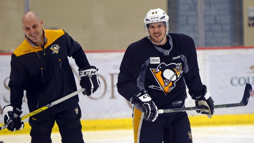 Pittsburgh Penguins' Sidney Crosby, right, skates past assistant coach Rick Tocchet  during NHL practice, Friday, May 5, 2017, at the team's practice facility in Cranberry, Pa. It was Crosby's first time back on the ice since he suffered a concussion in Game 3 of Pittsburgh's playoff series against Washington. It's still uncertain whether he will be available for Game 5 on Saturday night in Washington.  (AP Photo/Keith Srakocic)