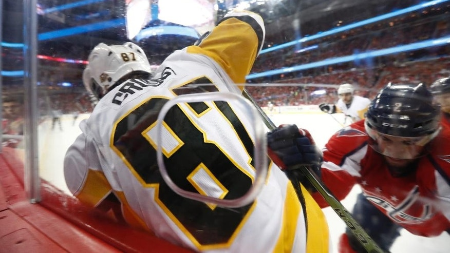 Pittsburgh Penguins center Sidney Crosby (87) is checked into the boards by Washington Capitals defenseman Matt Niskanen (2) during the first period of Game 5 in the second-round of the NHL hockey Stanley Cup playoffs, Saturday, May 6, 2017, in Washington. The Capitals won 4-2. (AP Photo/Carolyn Kaster)