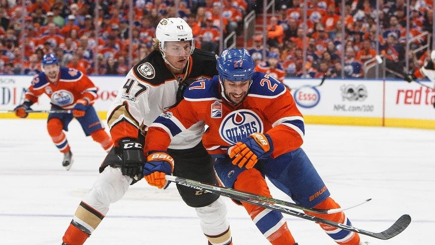 Anaheim Ducks' Hampus Lindholm (47) and Edmonton Oilers' Milan Lucic (27) battle for the puck during the second period in Game six of a second-round NHL hockey Stanley Cup playoff series in Edmonton, Alberta, Sunday, May 7, 2017. (Jason Franson/The Canadian Press via AP)