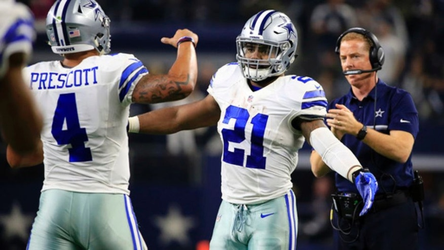 Dallas Cowboys' Dak Prescott (4) is congratulated on his touchdown run by Ezekiel Elliott (21) in the first half of an NFL football game against the Tampa Bay Buccaneers as head coach Jason Garrett, right, watches, , Sunday, Dec. 18, 2016, in Arlington, Texas. (AP Photo/Ron Jenkins)