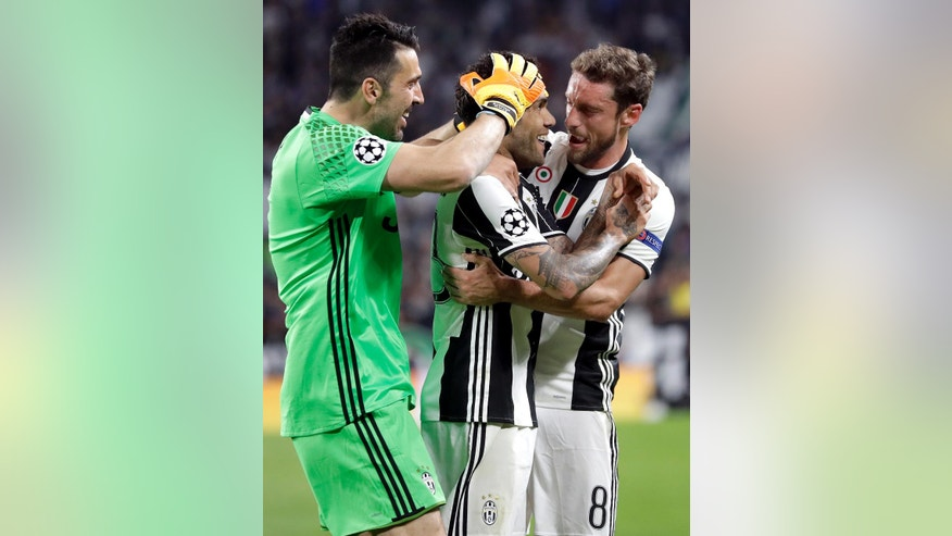 Juventus' scorer Dani Alves, center, and his teammates Claudio Marchisio, right, and Gianluigi Buffon, left, celebrate their side's 2nd goal during the Champions League semi final second leg soccer match between Juventus and Monaco in Turin, Italy, Tuesday, May 9, 2017. (AP Photo/Antonio Calanni)
