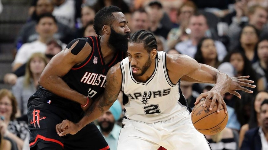 San Antonio Spurs forward Kawhi Leonard (2) works for an opportunity to the basket as Houston Rockets' James Harden, left, defends during the first half of Game 2 in a second-round NBA basketball playoff series, Wednesday, May 3, 2017, in San Antonio. (AP Photo/Eric Gay)