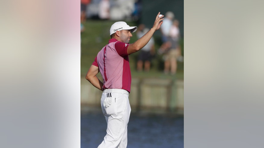 Sergio Garcia, of Spain, holds his ball after making a hole-in-one on the 17th hole, during the first round of The Players Championship golf tournament Thursday, May 11, 2017, in Ponte Vedra Beach, Fla. (AP Photo/Chris O'Meara)