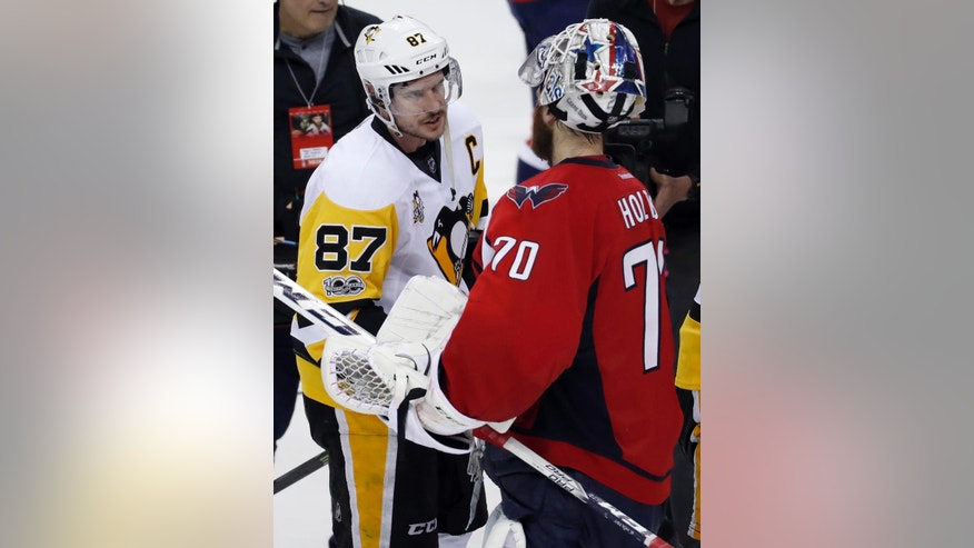 Pittsburgh Penguins center Sidney Crosby (87) talks with Washington Capitals goalie Braden Holtby (70) after Game 7 in an NHL hockey Stanley Cup Eastern Conference semifinal, Wednesday, May 10, 2017, in Washington. The Penguins won 2-0. (AP Photo/Alex Brandon)