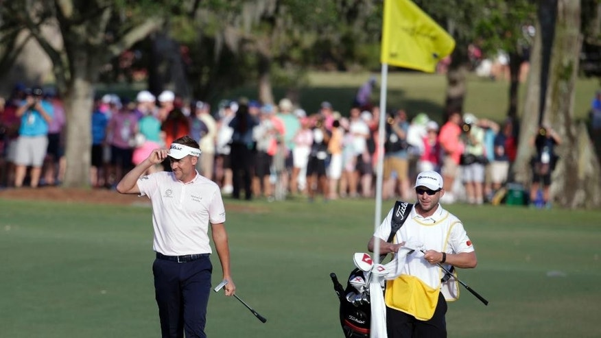 Ian Poulter of England, left, tips his hat as he approaches his ball on the 18th green, during the final round of The Players Championship golf tournament Sunday, May 14, 2017, in Ponte Vedra Beach, Fla. To the right is caddie James Walton. (AP Photo/Lynne Sladky)