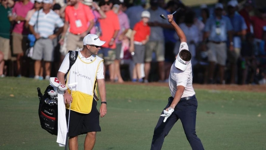 Ian Poulter of England, right, reacts to his shot from the 18th fairway , during the final round of The Players Championship golf tournament Sunday, May 14, 2017, in Ponte Vedra Beach, Fla. To the left is caddie James Walton. (AP Photo/Lynne Sladky)