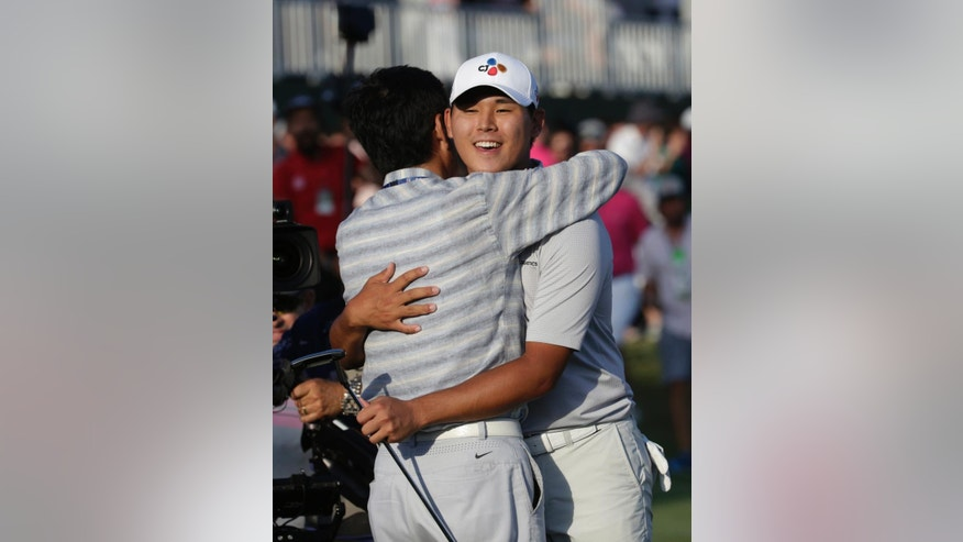 Si Woo Kim of South Korea, right, is hugged after winning The Players Championship golf tournament Sunday, May 14, 2017, in Ponte Vedra Beach, Fla. (AP Photo/Lynne Sladky)