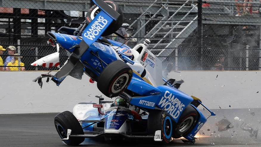 The car driven by Scott Dixon, of New Zealand, goes over the top of Jay Howard, of England, in the first turn during the running of the Indianapolis 500 auto race at Indianapolis Motor Speedway, Sunday, May 28, 2017, in Indianapolis. (