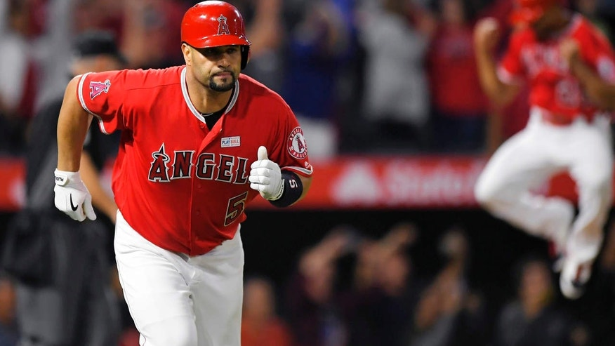 Los Angeles Angels' Albert Pujols, left, runs to first with a solo home run, the 600th homer of his career, while Ben Revere jumps in the background during the fourth inning of the team's baseball game against the Minnesota Twins, Saturday, June 3, 2017, in Anaheim, Calif.