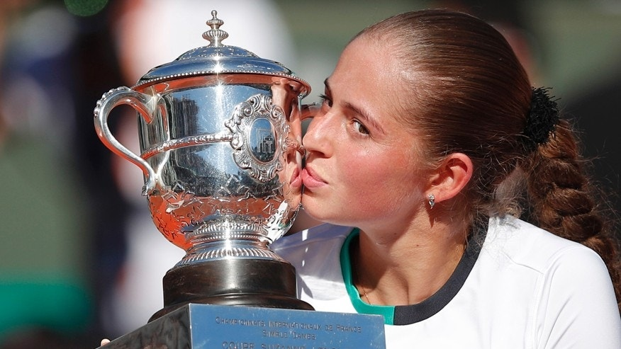 Latvia's Jelena Ostapenko kisses the trophy after winning the women's final match of the French Open tennis tournament against Romania's Simona Halep in three sets 4-6, 6-4, 6-3, at the Roland Garros stadium, in Paris, France, Saturday, June 10, 2017. (AP Photo/Christophe Ena)