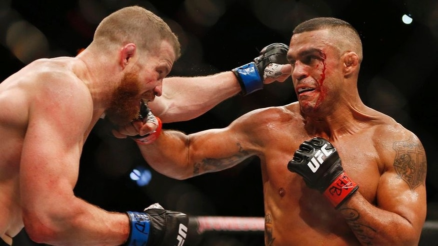 Vitor Belfort, right, of Brazil, trades blows with Nate Marquardt, of the United States, during their UFC middleweight mixed martial arts bout in Rio de Janeiro, Brazil, early Sunday, June 4, 2017. (AP Photo/Leo Correa)