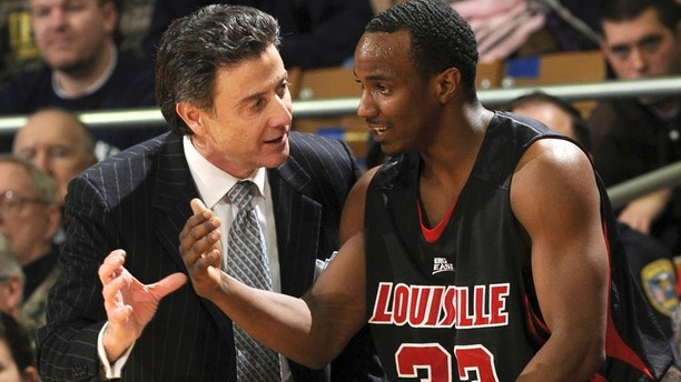 FILE - In this Feb. 12, 2009, file photo Louisville coach Rick Pitino, left, talks with guard Andre McGee during the first half of an NCAA college men's basketball game against Notre Dame in South Bend, Ind. A grand jury declined to indict an escort and former Louisville men's basketball staffer in a sex scandal that engulfed the program. The Jefferson County grand jury decided Thursday, May 25, 2017, there wasn't enough evidence for charges of prostitution and unlawful transactions with a minor against Katina Powell and Andre McGee. (AP Photo/Joe Raymond, File)