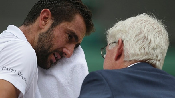 Croatia's Marin Cilic wipes his face as he has treatment on his foot as he takes a medical timeout during the Men's Singles final match against Switzerland's Roger Federer on day thirteen at the Wimbledon Tennis Championships in London Sunday, July 16, 2017. (Daniel Leal-Olivas/Pool Photo via AP)