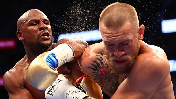Aug 26, 2017; Las Vegas, NV, USA; Floyd Mayweather Jr. lands a hit against Conor McGregor during their boxing match at the at T-Mobile Arena. Mandatory Credit: Mark J. Rebilas-USA TODAY Sports     TPX IMAGES OF THE DAY - RTX3DHOX