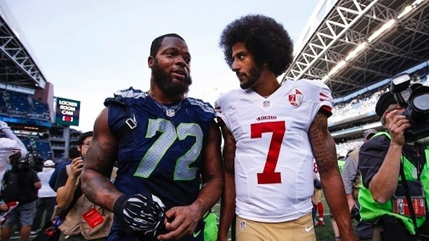 Sep 25, 2016; Seattle, WA, USA; San Francisco 49ers quarterback Colin Kaepernick (7) and Seattle Seahawks defensive end Michael Bennett (72) talk following a 37-18 Seattle victory at CenturyLink Field. Mandatory Credit: Joe Nicholson-USA TODAY Sports - 9566205
