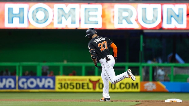 FILE - In this Sept. 2, 2017, file photo, Miami Marlins' Giancarlo Stanton rounds second base after hitting a home run during the first inning of a baseball game against the Philadelphia Phillies, in Miami. Nearly two decades after the height of the Steroids Era, Major League Baseball is on track to break its season record for home runs on Tuesday with nearly two weeks left in the season. There were 5,663 home runs hit through Sunday, 30 shy of the record 5,693 set in 2000. (AP Photo/Wilfredo Lee, File)