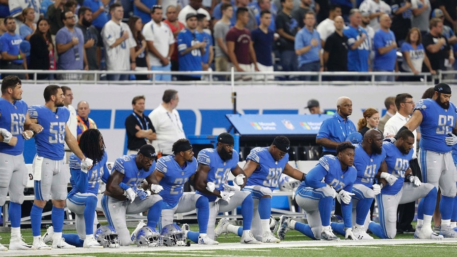 Members of the Detroit Lions lock arms or kneel at Sunday's game against the Atlanta Falcons.