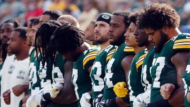 "FILE - In this Sunday, Sept. 24, 2017, file photo, members of the Green Bay Packers lock arms during the national anthem before an NFL football game against the Cincinnati Bengals in Green Bay, Wis. The Packers plan to lock arms during the national anthem before Thursday night's game against the Chicago Bears, and they are asking fans to do the same in what they say will be a ""moment of unification."" (AP Photo/Mike Roemer, File"