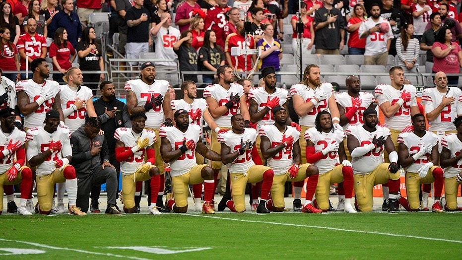 Members of the San Francisco 49ers kneeling during the National Anthem Sunday before their game against the Arizona Cardinals.