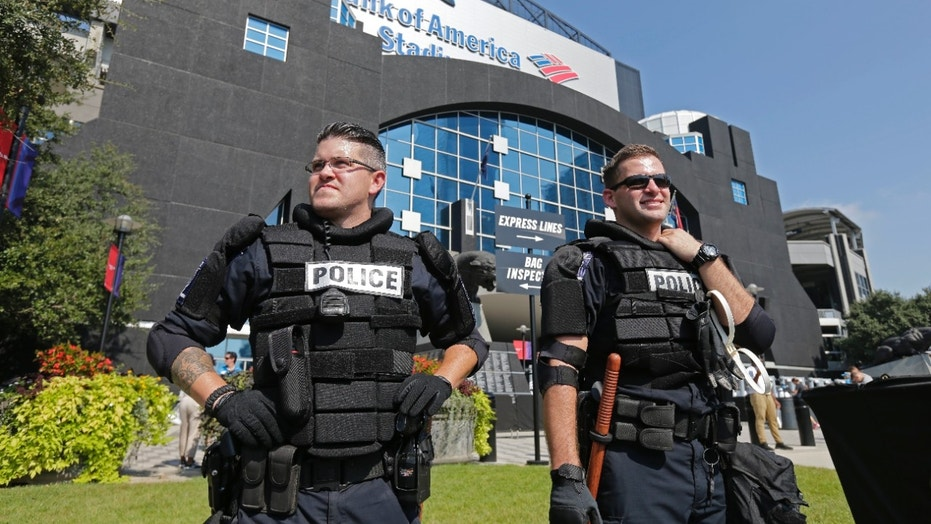 Police officers stand guard outside Bank of America Stadium before an NFL game.