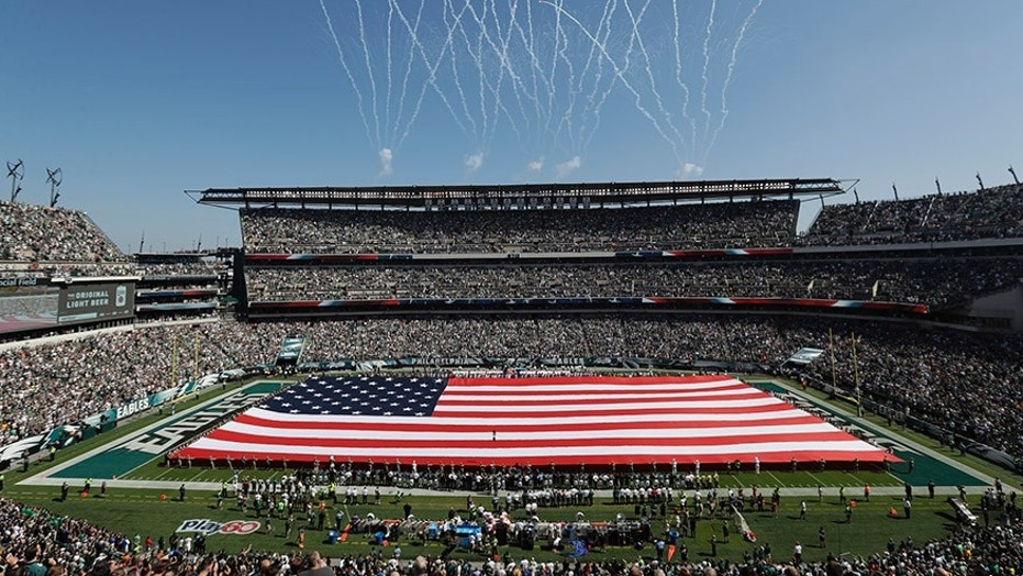 An American flag covers the field before an NFL game between the Philadelphia Eagles and the New York Giants in Philadelphia.