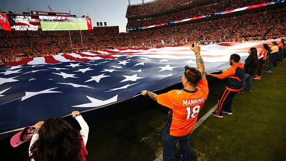 People hold a flag before an NFL football game between the Denver Broncos and the New York Giants, Oct. 15, 2017, in Denver.