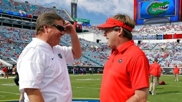 Florida head coach Jim McElwain, left, and Georgia head coach Kirby Smart greet each other at midfield before an NCAA college football game, Saturday, Oct. 28, 2017, in Jacksonville, Fla. (AP Photo/John Raoux)