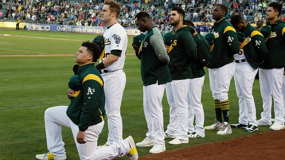 Oakland Athletics catcher Bruce Maxwell kneels during the national anthem before a game in Oakland, Calif., Sept. 23, 2017.