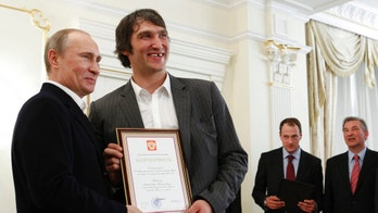 "FILE - In this May 29, 2012, file photo, Russian national ice hockey team member Alexander Ovechkin, right, holds a certficate of recognition given to him by President Vladimir Putin, left, in the Novo-Ogaryovo residence outside Moscow. Washington Capitals captain Alex Ovechkin has voiced his support for Vladimir Putin ahead of the upcoming Russian presidential elections. Ovechkin posted a message in Russian on his Instagram account Thursday, Nov. 2, 2017,  announcing he's starting ""a social movement called Putin Team."" From right in the background are Russian ice hockey federation president Vladislav Tretyak and Russia's captain Ilya Nikulin. (AP Photo/Sergei Karpukhin, Pool, File)"