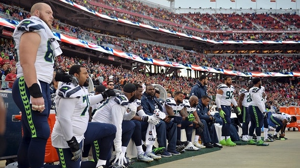 FILE - In this Nov. 26, 2017, file photo, Seattle Seahawks players sit and kneel during the playing of the national anthem before an NFL football game against the San Francisco 49ers, in Santa Clara, Calif. President Donald Trump is renewing his complaints about NFL players who kneel during the national anthem. Players have been kneeling to protest racism and police brutality, particularly toward people of color. Trump says the act is disrespectful and is hurting the game.(AP Photo/Don Feria, File)