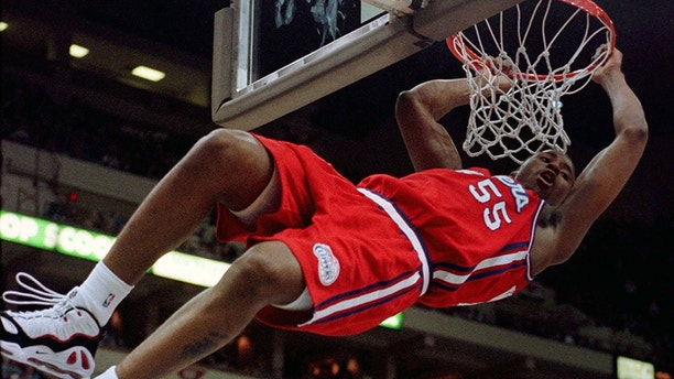 Los Angeles Clippers' Lorenzen Wright swings on the rim after dunking an errant shot by teammate Lamond Murray during the first half against the Minnesota Timberwolves January 19.