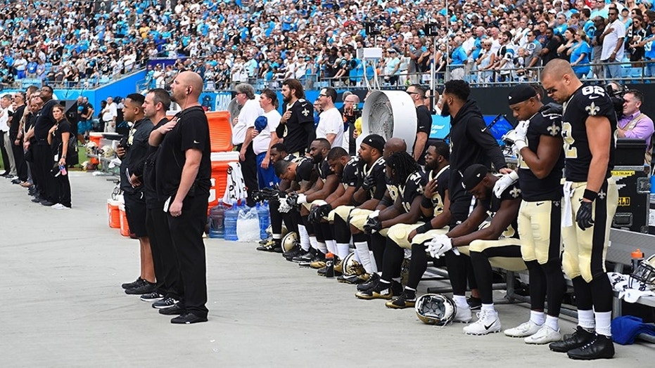 New Orleans Saints players stand and sit during the national anthem at Bank of America Stadium in Charlotte, N.C. on Sept. 24.