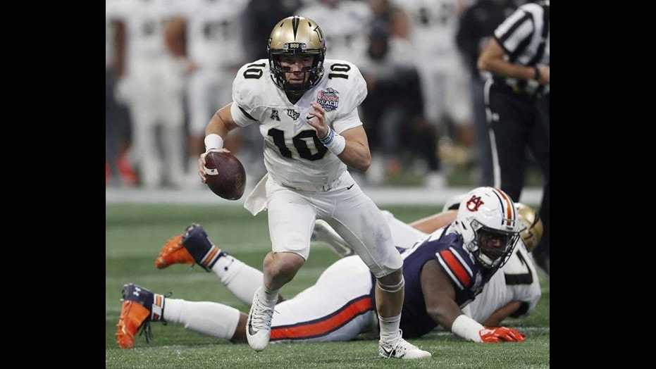 Central Florida quarterback McKenzie Milton (10) runs out of the pocket against Auburn during the first half of the Peach Bowl NCAA college football game Monday in Atlanta. (AP Photo/John Bazemore)