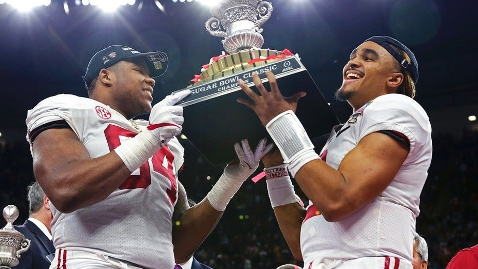 Alabama players D'Ron Payne, left, and Jalen Hurts hoist the Sugar Bowl trophy after Monday night's victory.