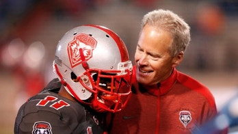 New Mexico's Ridge Jones is congratulated by coach Bob Davie after Jones ran for a 75-yard kick off return against Boise State in the first half of an NCAA college football game, Saturday, Nov. 8, 2014 in Albuquerque, N.M. (AP Photo/Eric Draper)