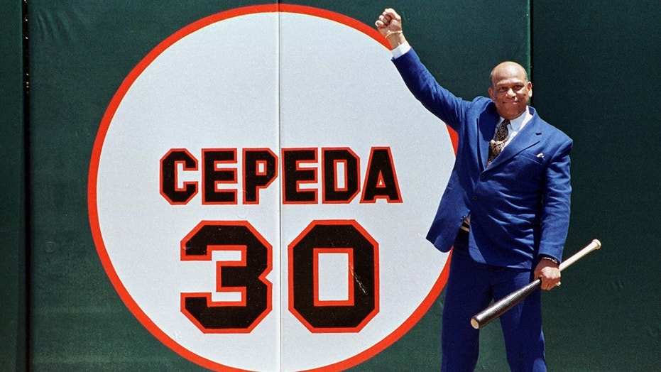 Former San Francisco Giants star Orlando Cepeda pumps his fist in the air as he stands in front of his old number 30 painted on the right field wall during a ceremony at 3Com Park July 11 in which his number was retired. Cepeda will be inducted into the Baseball Hall of Fame in Cooperstown, New York in two weeks.