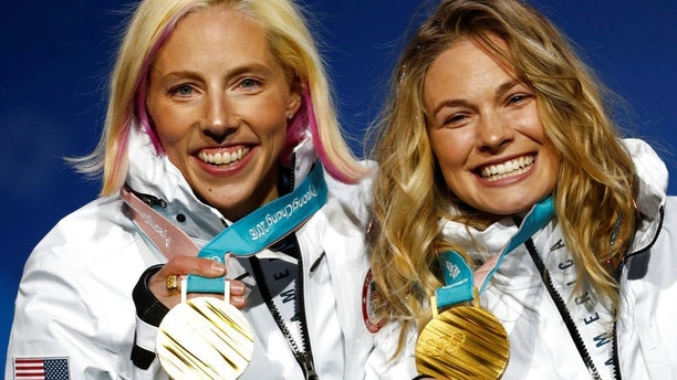 Gold medalists in the women's team sprint freestyle cross-country skiing Kikkan Randall and Jessica Diggins, of the United States, pose during the medals ceremony at the 2018 Winter Olympics in Pyeongchang, South Korea, Thursday, Feb. 22, 2018. (AP Photo/Patrick Semansky)
