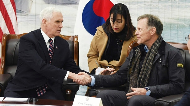 U.S. Vice President Mike Pence, left, shakes hands with Fred Warmbier, the father of Otto Warmbier, an American who died last year, days after his release from captivity in North Korea, at the Cheonan Memorial in Pyeongtaek, South Korea, Friday, Feb. 9, 2018. Pence is using his appearance at the Winter Olympics to call on the international community to grow tougher on North Korea's nuclear program and human rights abuses. (Korea Pool/Yonhap via AP)