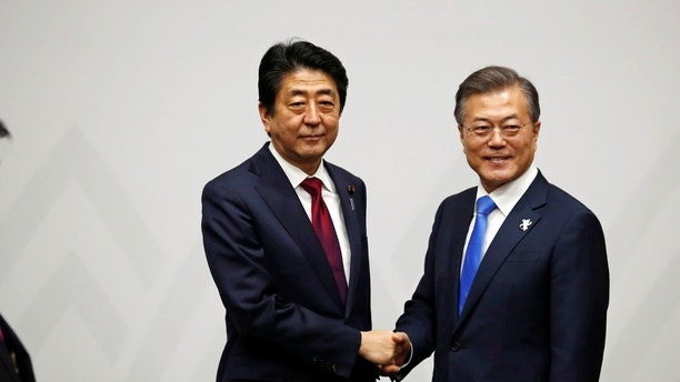 South Korean President Moon Jae-in shakes hands with Japanese Prime Minister Shinzo Abe during their meeting in Pyeongchang, South Korea February 9, 2018. REUTERS/Kim Hong-Ji - RC1E4ED83050