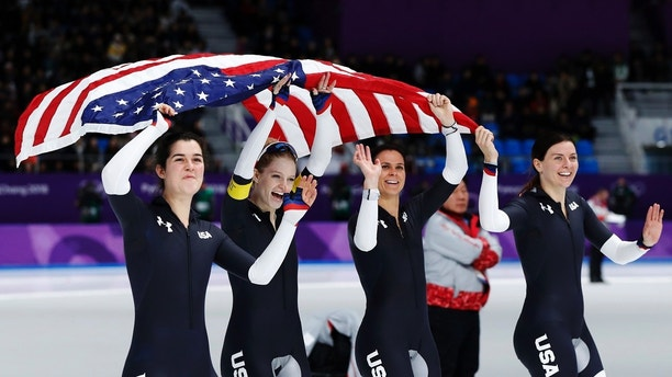 Bronze medalist team U.S.A. with Carlijn Schoutens, Mia Manganello, Brittany Bowe and Heather Bergsma, from left to right, celebrate after the women's team pursuit speedskating race at the Gangneung Oval at the 2018 Winter Olympics in Gangneung, South Korea, Wednesday, Feb. 21, 2018. (AP Photo/Petr David Josek)