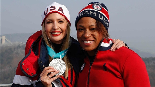 Silver medalist of the women's two-man bobsled, Lauren Gibbs of the United States, right, poses for photos with Ivanka Trump during the four-man bobsled competition final at the 2018 Winter Olympics in Pyeongchang, South Korea, Sunday, Feb. 25, 2018. (Eric Gaillard/Pool Photo via AP)