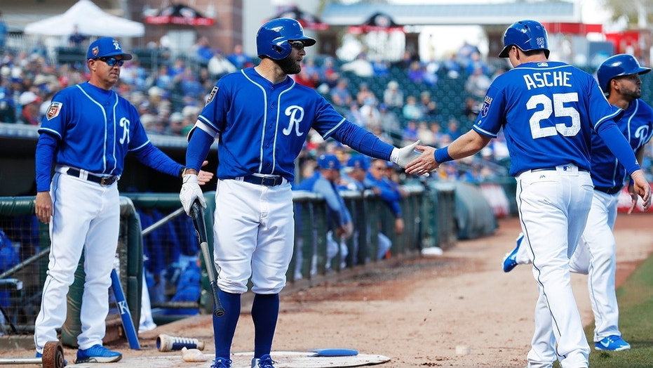 Kansas City Royals' Cody Asche (25) is greeted by teammate Tyler Collins, center, after scoring a run during the fifth inning of a spring training baseball game against the Cincinnati Reds, Wednesday, Feb. 28, 2018, in Surprise, Ariz.