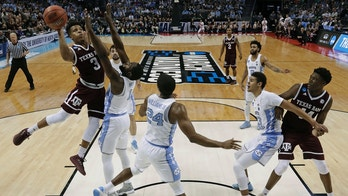 Texas A&M's Admon Gilder (3) shoots against North Carolina's Theo Pinson (1) during the first half of a second-round game in the NCAA men's college basketball tournament in Charlotte, N.C., Sunday, March 18, 2018. (AP Photo/Gerry Broome)