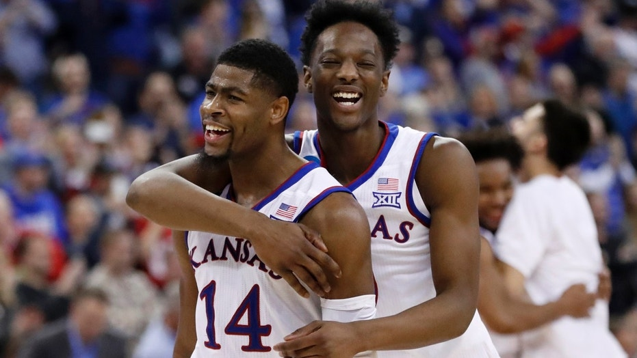 Kansas&#x27 Malik Newman and Marcus Garrett celebrate after defeating Duke 85-81 in overtime a regional final game in the NCAA men's college basketball tournament Sunday