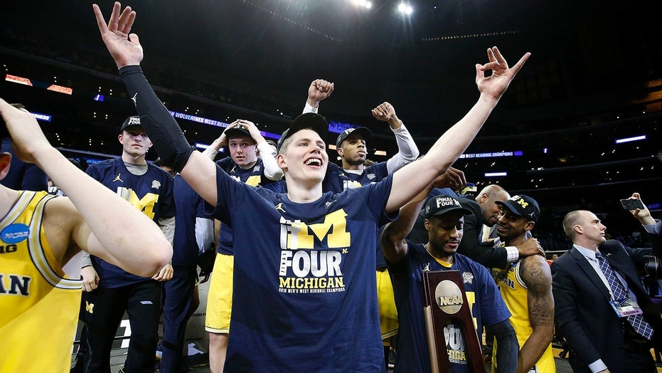 Michigan forward Moritz Wagner, foreground, and teammates celebrate after defeating Florida State 58-54 in an NCAA men's college basketball tournament regional final, in Los Angeles, March 24, 2018.