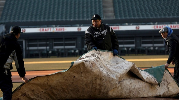 White Sox groundskeeper Nevest Coleman, center, helps Harry Smith Jr., left, and Jerry Powe with the tarp at Guaranteed Rate Field in Chicago,Monday, March 26, 2018. The Chicago Tribune reports that DNA evidence led prosecutors last year to vacate the conviction of 49-year-old Nevest Coleman. He'd been convicted in a 1994 rape and murder. He was released from prison in November and declared innocent last month. (Nancy Stone/Chicago Tribune via AP)
