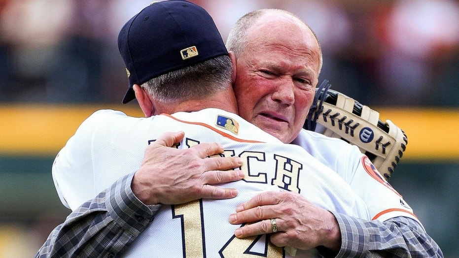 Rich Dauer embraces A.J. Hinch after throwing out the ceremonial first pitch.