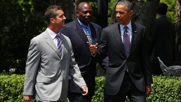 U.S. President Barack Obama (R) walks with Baltimore Ravens coach John Harbaugh (L) and team general manager Ozzie Newsome to a ceremony where Obama honored the 2013 NFL Superbowl winners during a ceremony on the South Lawn of the White House in Washington, June 5, 2013.   REUTERS/Jason Reed    (UNITED STATES - Tags: SPORT FOOTBALL POLITICS) - GM1E966037R01